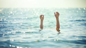 Foto di due braccia che svettano dall'acqua luccicante