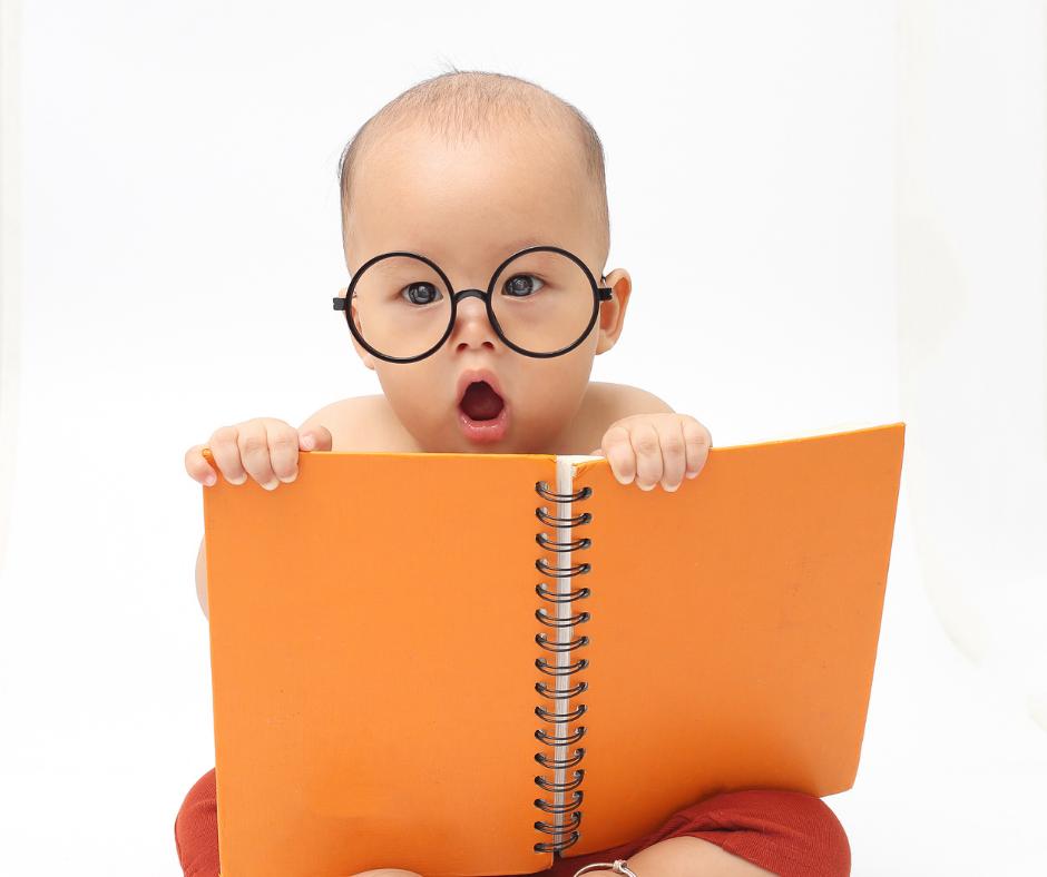 Foto di Bambino di circa un anno, con espressione sorpresa e con in mano un quaderno a spirale