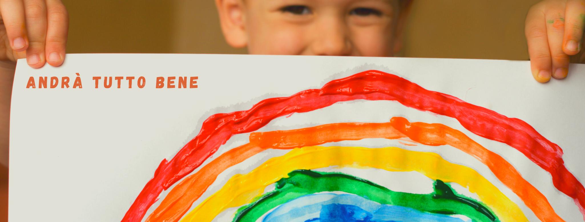 """Imamgine di un bambino che tiene nelle mani un disegno di un arcobaleno """"Andrà tutto bene"""""""